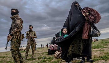 Member of the Syrian Democratic Forces stand guard as a woman walks with a child after leaving the Islamic State's last holdout of Baghouz, Syria, February 27, 2019.
