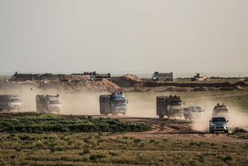 Trucks transporting people evacuated from the Islamic State group's embattled holdout of Baghouz ride in a field on February 25, 2019.