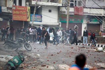 Protestors throw stones during a clash between Hindu and Muslim communities while protesting against a Pakistan-backed group's attack on a paramilitary convoy killing 40 in Kashmir, in Jammu, India. Feb. 15, 2019