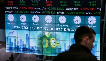 File photo: A man stands in front of an electronic board displaying market data at the Tel Aviv Stock Exchange in Israel, January 29, 2017.