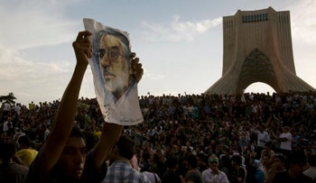 File photo: A demonstrator shows a picture of former presidential candidate Mir Hossein Mousavi during a rally in western Tehran, June 15, 2009.