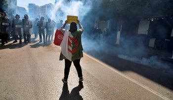A woman holds a sign as police fire tear gas at protesters demonstrating in the streets of Algiers, Algeria, to denounce President Abdelaziz Bouteflika's bid for a fifth term, March 1, 2019.