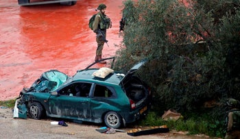 Israeli forces stand guard next to a destroyed car, after two Palestinian were shot dead as they ran over troops in Kafr Nama, northwest of Ramallah, on March 4, 2019.
