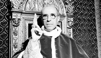 Pope Pius XII, wearing the ring of St. Peter, raises his right hand in a papal blessing at the Vatican, September 1945.