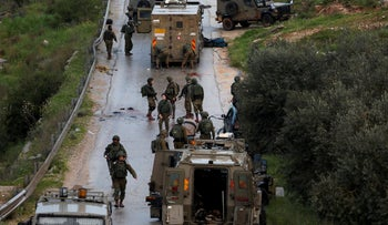 Israeli soldiers gather at the scene of a car ramming near Ramallah, in the West Bank, March 4, 2019.