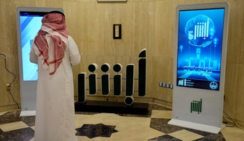 A Saudi Ministry employee stands in front of a screen displaying the Absher mobile app logo, Riyadh, February 19, 2019.