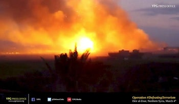 A large explosion is seen as Kurdish fighters fire weapons at Islamic State held territory in Baghouz, eastern Syria in this still image taken from a video published March 4, 2019