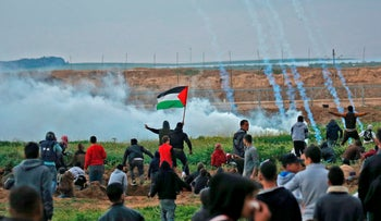 Palestinians run through tear gas fumes during clashes following a demonstration along the border with Israel east of Gaza City on March 1, 2019.