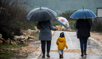 Walking through the rain in Bet Zayit, Jerusalem, March 2, 2019.