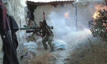 A rebel fighter gestures as he shoots his weapon during clashes with forces loyal to Syria's President Bashar al-Assad on the frontline of Aleppo's Sheikh Saeed neighbourhood May 23, 2015
