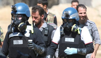 File photo: UN chemical weapons experts wearing gas masks carry samples from one of the sites of an alleged chemical weapons attack in Damascus August 28, 2013.