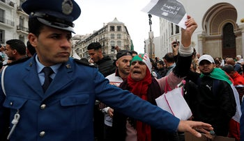 A police officer stands guard as people protest against Algerian President Abdelaziz Bouteflika, Algiers, Algeria, March 8, 2019.