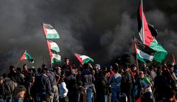 Palestinian protesters wave flags amid smoke from burning tires during clashes with Israeli soldiers following a demonstration near the Israel-Gaza fence, east of Gaza City, on March 8, 2019. (Photo by
