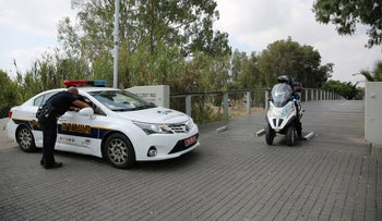 For illustration: A policeman and police car in Israel.