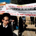 Ultra-Orthodox Jewish men stand with protest banners outside the Western Wall in Jerusalem on March 8, 2019.