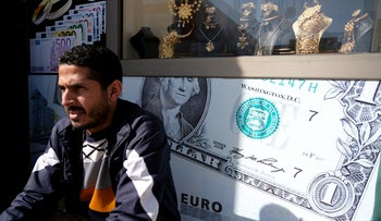 A man sits next to a gold shop and a currency exchange in Benghazi, Libya February 4, 2019.