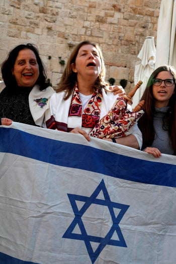 Women of the Wall head Anat Hoffman, center, wearing a traditional Jewish prayer shawl and holding onto Torah scrolls during the Rosh Hodesh event marking the organization's 30th anniversary at the Western Wall, Jerusalem, March 8, 2019.