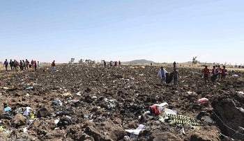 Rescue team collect bodies in bags amid debris at the crash site of Ethiopia Airlines near Bishoftu, a town some 60 kilometres southeast of Addis Ababa, Ethiopia, on March 10, 2019