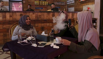Palestinian student Saly Abu Amra (L), 23, a university student majoring in Sharia (Islamic Law) and Law, looks on as her friend smokes a water pipe at a cafe, in Gaza City, December 4, 2018