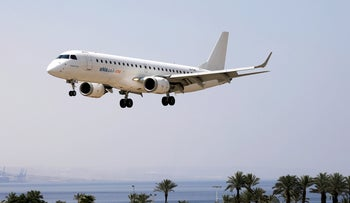 An airplane flies over the Eilat Airport, Israel, June 13, 2018.