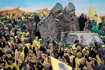 Hezbollah fighters stand atop a truck mounted with mock rockets during a rally in Nabatiyeh, Lebanon, October 27, 2015.