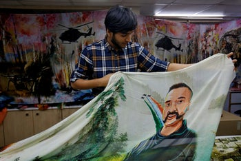 A salesman displays a sari printed with an image of Indian Air Force pilot Abhinandan Varthaman, captured and later released by Pakistan. Surat, India, March 8, 2019