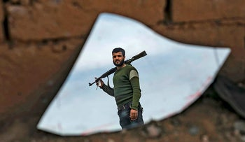 The image of fighter with the Syrian Democratic Forces (SDF) is reflected on a broken mirror in the town of Baghouz, on the frontline of fighting to expel the Islamic State group from the area, in the eastern Syrian province of Deir Ezzor, on March 12, 2019