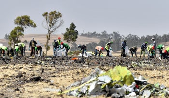 A crew works with an investigative team to clear the site after the crash of the Ethiopian Airlines in the Oromia region, March 13, 2019.