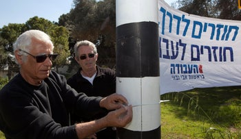 """Avraham Mencher Dvori, left, and Tzvi Alon attaching a Labor Party banner to a post at Kibbutz Be'eri. It reads """"Getting back on track. Coming back to Labor."""""""