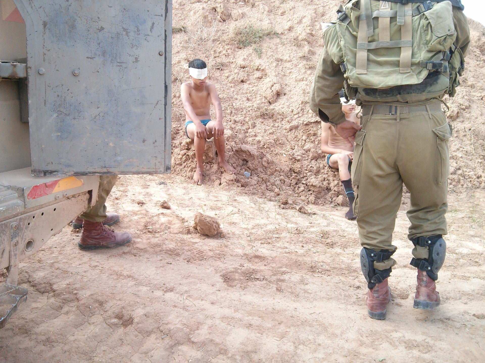 Young Palestinian detainees under guard. Soldiers typically burst into the house in the middle of the night, seize the wanted youth and leave the family with a document stating where he's being taken.