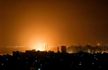 The sky glows orange during an Israeli airstrike in Gaza City, March 15, 2019.