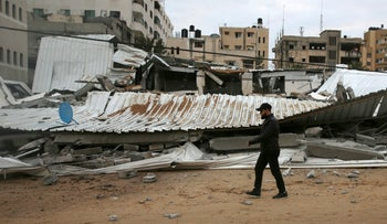 A Palestinian inspects the damage of destroyed building belongs to Hamas ministry of prisoners hit by Israeli airstrikes in Gaza City, early Friday, March 15, 2019.