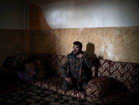 SDF fighter Dia Hassakeh looks out of a building in Baghouz, Syria, February 18, 2019.