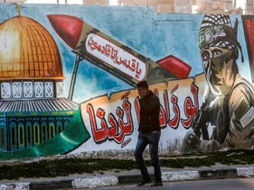 """A Palestinian walks past a mural depicting a masked fighter of the Qassam Brigades, Hamas' armed wing, and a missile with the Arabic caption: """"Oh Jerusalem, we are coming."""" Rafah, Gaza. March 14, 2019"""