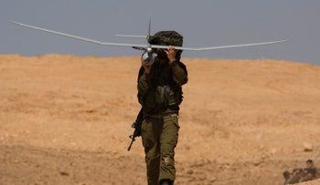 FILE Photo: An Israeli soldier carries a drone during a large military exercise at the Shizafon Armored Corps Training Base in the Arava desert, north of Eilat.