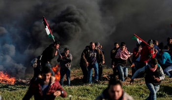 File photo: Palestinian protesters walk past burning tyres during clashes with Israeli soldiers along the border with Israel, east of Gaza City, March 8, 2019.
