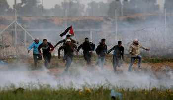 Palestinian demonstrators run away from Israeli fire and tear gas during a protest at the Israel-Gaza border fence, in the southern Gaza Strip February 15, 2019.