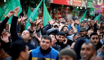 Palestinian Hamas supporters try to catch sweets as they celebrate the West Bank shooting attack, in the northern Gaza Strip, March 17, 2019.