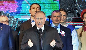Russian President Vladimir Putin, center, gestures while speaking at an outdoor concert in Crimea's regional capital of Simferopol, Crimea, Monday, March 18, 2019