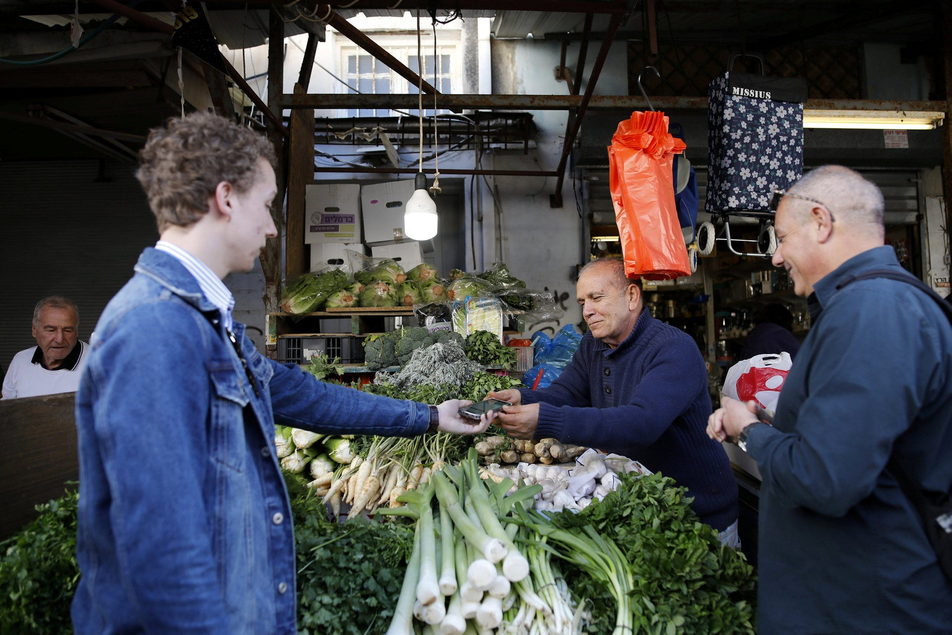At the Carmel market in Tel Aviv, tourists and a market vendor participate in a special training session as part of the initiative by the municipality.