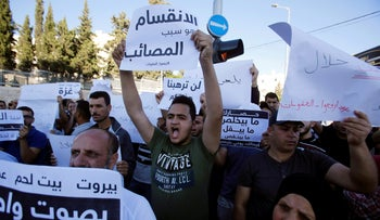 """File photo: Palestinian demonstrator holds a sign that reads """"division is the reason for adversities"""" during a protest demanding Abbas to lift sanctions on Gaza, the West Bank, June 20, 2018."""