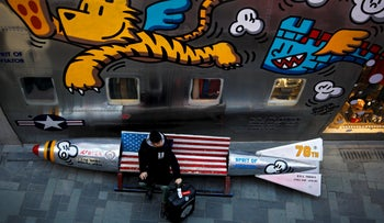 "A man with his luggage sits on a bench in a shape of a mocked aerial bomb and a U.S. flag outside a fashion boutique selling U.S. brand clothing at the capital city's popular shopping mall in Beijing, Friday, Feb. 1, 2019. U.S. President Donald Trump expects to meet with his Chinese counterpart Xi Jinping to try to resolve a six-month trade standoff after U.S. and Chinese negotiators ended two days of talks Thursday without settling the toughest issues that divide the world's two biggest economies. The White House says the two countries made progress but ""much work remains to be done."""