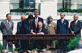 Shimon Peres signs the Oslo Accords, watched by Andrei Kozyrev, Yitzhak Rabin, President Bill Clinton, Yasser Arafat, Warren Christopher and Mahmoud Abbas, Washington, D.C., September 13, 1993