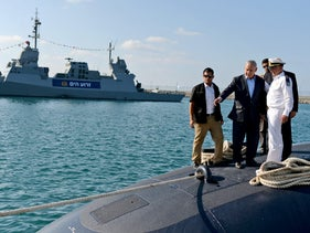 Prime Minister Benjamin Netanuyahu stands on top of a new submarine, 'INS Tanin,' at Haifa port, September 23, 2014.