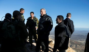 FILE PHOTO: Israel's Prime Minister Benjamin Netanyahu chats with Israeli soldiers at a military outpost during a visit to Mount Hermon in the Israeli-occupied Golan Heights in February 2015.