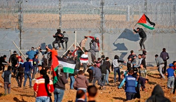 Palestinians protest with Palestinian flags as they try to climb the barbed-wire fence by the border with Israel, Gaza City, March 22, 2019.
