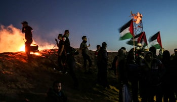 Palestinian protesters take part in a night demonstration near the fence along the border with Israel on March 19, 2019.