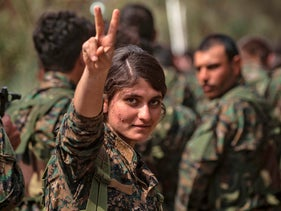 A female fighter of the U.S.-backed Kurdish-led Syrian Democratic Forces flashes the victory sign while celebrating the elimination of ISIS' last bastion, Deir Ezzor, Syria, March 23, 2019.