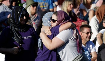 People embrace in a show of love during a vigil in Hagley Park following the March 15 mass shooting in Christchurch, New Zealand, March 24, 2019.