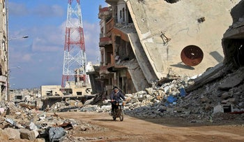 A Syrian man rides his motorcycle past damaged buildings in the southern city of Daraa, on March 16, 2017